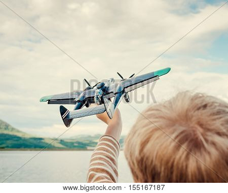 Child holds a model of a plane in his hand