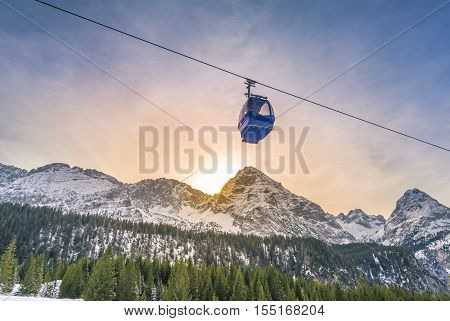 Cable car route over the Alps mountains - Cable car route going over the Austrian alps mountains with their fir forests while the sun sets down behind the peaks. Image taken in Ehrwald Austria.