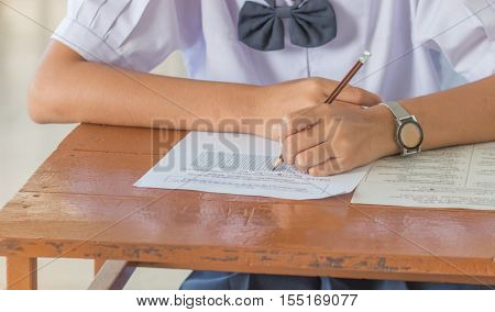 students writing a test exercise exam paper and multi-choice in classroom uniform student in Thailand.