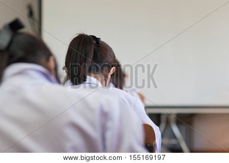 Asian girl students reading and writing a test in exercise exam in classroom : education concept