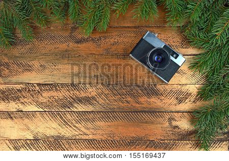 The old camera on a wooden background and twigs of Christmas tree. Christmas background.