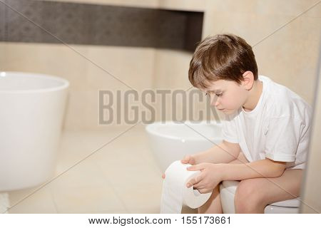 Little 7 Years Old Boy Sitting On Toilet.