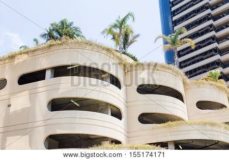 Circular Concrete Parking Garage in Tropics with Palm Trees