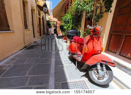 Rethymnon, Island Crete, Greece - July 1 2016: A red old parked scooter and a local citizen in the end of the narrow street of the old town's part of city Rethymnon