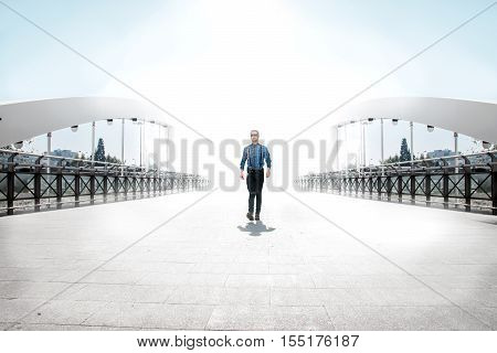 Utopic concept - Man walking from the light on a bridge