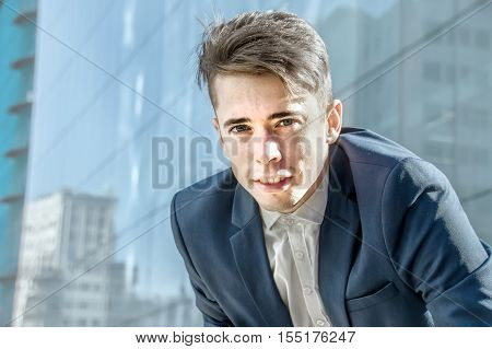 Smart looking handsome young business man portrait over office building background