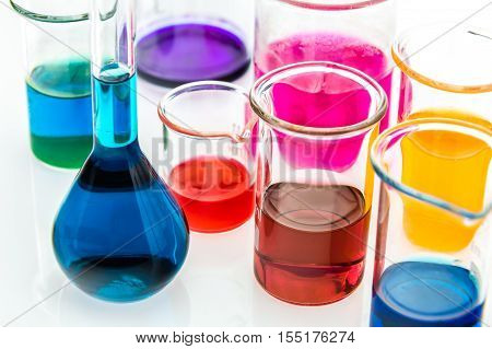 various beakers with different types of indicators in acids and basis four colors of indicators in several solutions