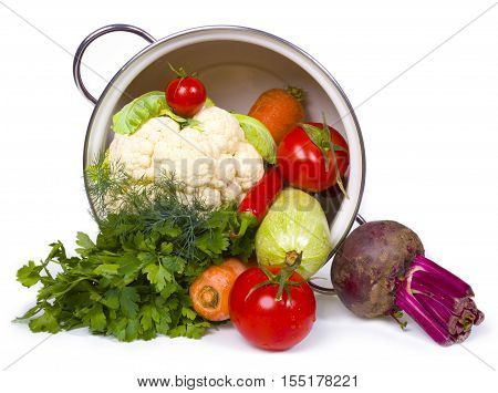 Fresh vegetables in overturned pot isolated on white background