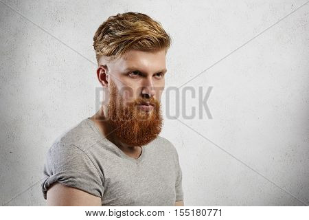 Half-profile Studio Shot Of Handsome Brutal Bearded Man Wearing Gray T-shirt With Rolled Up Sleeves