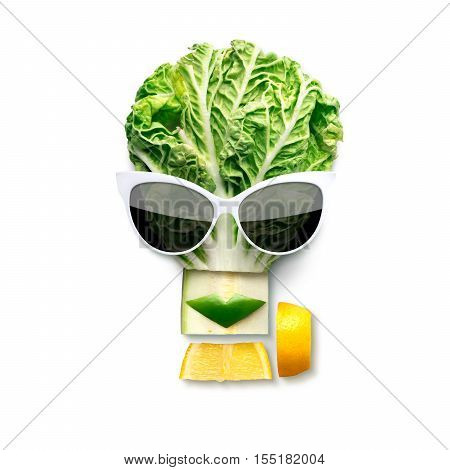 Quirky food concept of cubist style female face in sunglasses made of fruits and vegetables isolated on white.