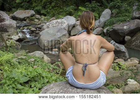 Woman meditating in nature in front of the river with stones and rocks riverbed and forest greenery. Pure nature landscape with fresh water current. Hiking in wild place. Swimming in fresh river