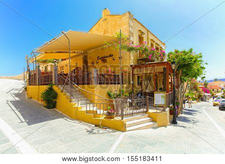 Rethymnon, Island Crete, Greece - July 1 2016: Cozy small cretan cafe with open veranda with flowers and colorful stairs