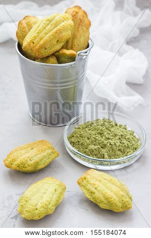 Homemade matcha green tea madeleines on the table and in metal bucket vertical