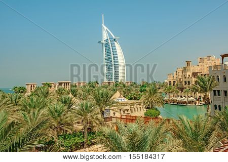 DUBAI, UAE - OCTOBER 14, 2016: A different view of the iconic Burj al Arab set against green palm trees and the artificial lake in Al Qasr Hotel