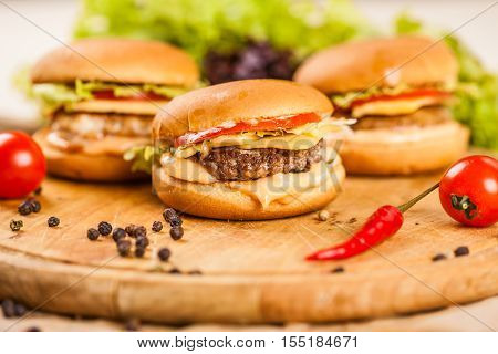 Three mini burgers with beef on wooden board