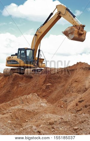 track-type loader excavator machine doing earthmoving work at sand quarry