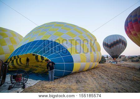 Cappadocia Turkey - September 25 2016: Color image of hot air balloons preparing to take off in Cappadocia Turkey at sunrise.