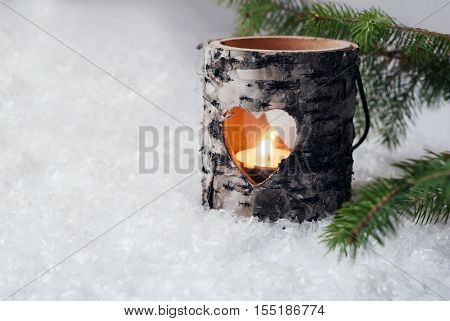 Wood candle holder in the snow with pine