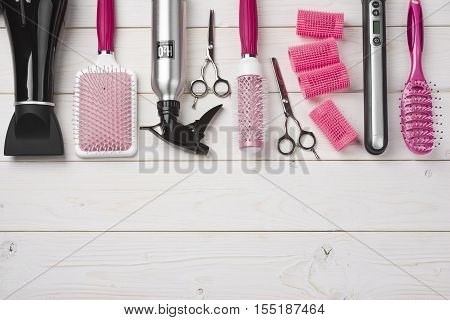 Professional hairdresser tools on wooden planks background with copy space