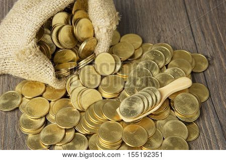 Gold Coins In Wood Spoon With Brown Sack Of Coins