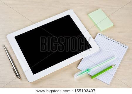 Tablet pc with notes pen and pensils on table surface
