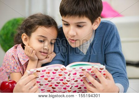 Two Children Reading Book At Home