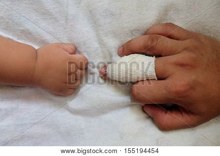 Close up of finger must have wound with gauze bandage and son hand