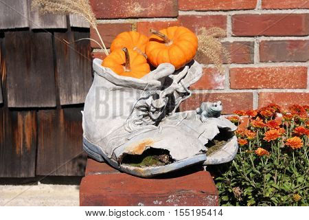 Pottery in the shape of a pair of old worn out boots filled with tiny orange pumpkins.