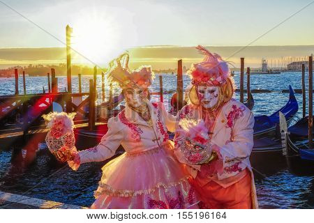 Famous carnival masks against gondolas in Venice Italy