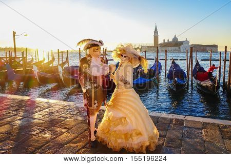 Famous carnival masks against gondolas in Venice Italy