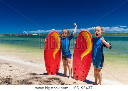 Young surfer twin brothers have fun on beach learning to surf