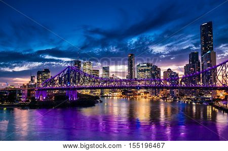 Vibrant night time panorama of Brisbane city with purple lights on Story Bridge, Australia