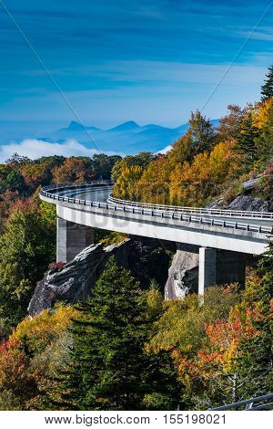 The Curve of Linn Cove Viaduct in Fall with wispy clouds in the valley