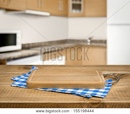 Wooden cutting board blue checkered towel over blurred kitchen background
