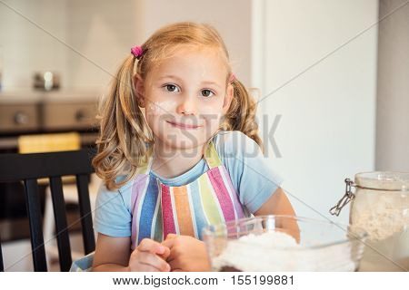 Portrait Of Pretty Little Girl Preparing Christmas Sweets In Kitchen