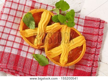 apricot cakes with lattice on top on checkered dishtowel