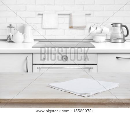 Wooden table with towel over defocused rustic kitchen bench background