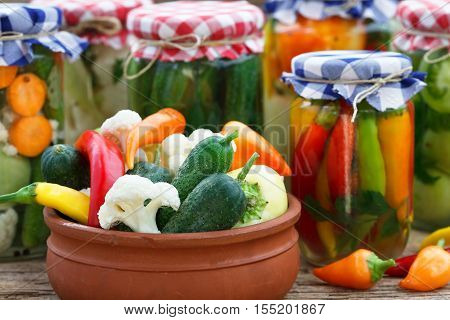 Preserved food in glass jars and old bowl. Various autumn marinaded food.