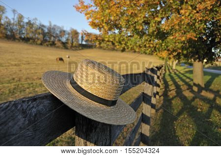 Closeup of traditional Amish straw hat in front of horse farm in the fall