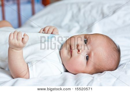 Cute Little Child Is Lying On The Sheet