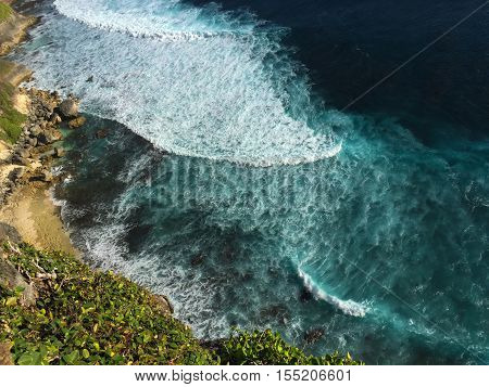 Blue wave of rip curl from the ocean splashes on yellow sand beach. Tropical sea danger. Surfing seashore from above. Helicopter view to the exotic island. Sea water. Nautical landscape