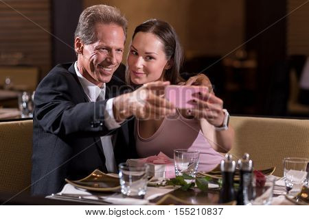 Full of delight. Smiling merry delighted couple taking a selfie while sitting at the table in the restaurant and expressing joy