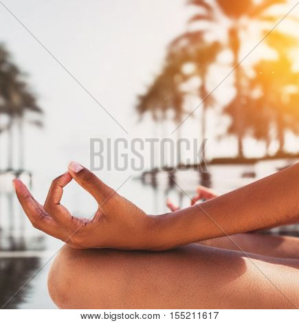 Young woman meditating by the glow of the rising sun sitting at the edge of a pool surrounded by tropical palm trees, close up on her hands and graceful gesture