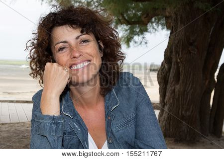 Happy Woman With Brown Hair In Her Fourties Smilling Outdoors