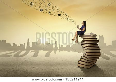 Image of pretty entrepreneur sending messages by using a laptop while sitting on a pile of book with number 2017