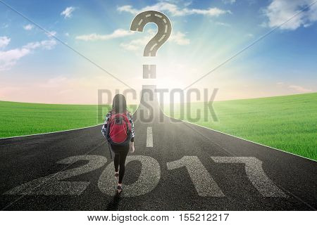 College student walking on the empty road with number 2017 while looking at question mark