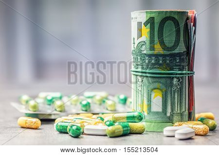 Euro money and medicaments. Euro coins and pills. Rolled euro banknotes stacked on each other in different positions and freely pills around scattered. Toned image.