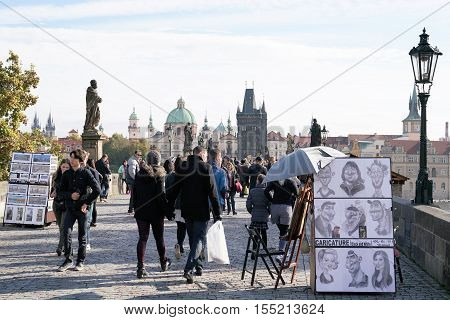 PRAGUE, CZECH REPUBLIK - OCTOBER 21, 2016: Tourists and artists on the Charles Bridge in Prague. The medieval Charles Bridge is one of the most famous sights in Prague  and is visited daily by thousands of tourists