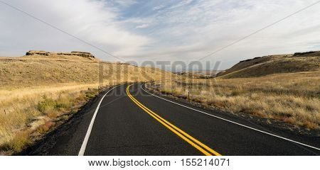 Two Lane blacktop road leads through scenic Oregon State