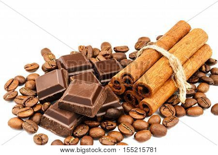 Dark chocolate bar cubes cinnamon sticks and coffee beans isolated on white background